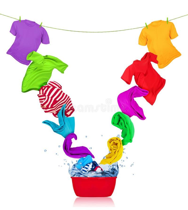 Bunte T-Shirts fliegt aus der Wäschereischüssel heraus stockbild