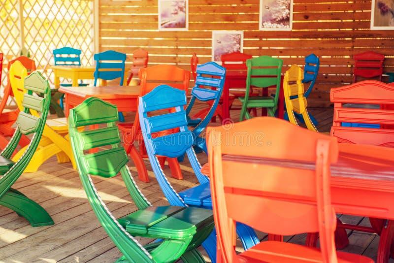Bunte Tabelle und Stühle bereit zu einem Café oder zu einem Restaurant Sommerterrassencafé, bunte multi farbige Plastikstühle dra lizenzfreie stockfotografie