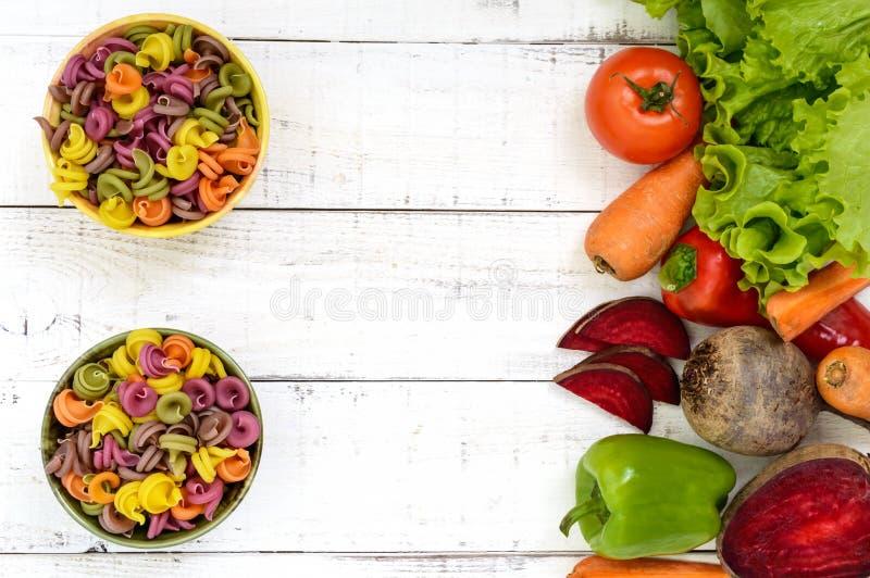 Bunte Teigwaren in Schüsseln auf einem weißen hölzernen Hintergrund, mit Frischgemüseroten rüben, Grüns, Karotten, Tomaten, Pfeff stockfoto