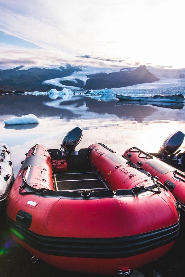 Bunte Tierkreisboote auf der Strandküste des vulkanischen Felsens und der Steine des schwarzen Sandes in der Gletscherlagune Fjal lizenzfreie stockbilder