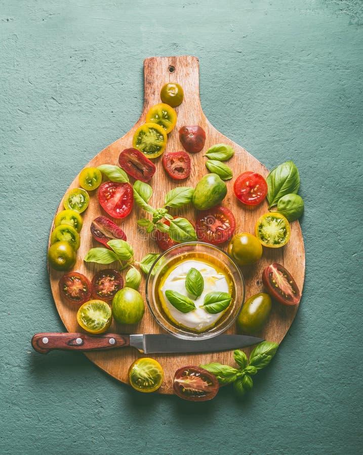Bunte Tomaten mit Basilikumblättern und -mozzarella in der Schüssel mit Olivenöl auf rundem hölzernem Schneidebrett, Draufsicht I stockbilder