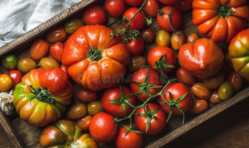 Bunte Tomaten von verschiedenen Größen und von Arten im dunklen hölzernen Behälter lizenzfreie stockfotos