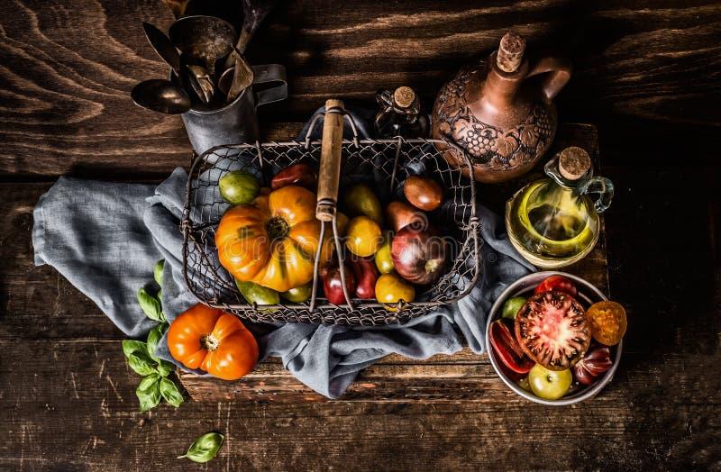 Bunte Tomaten, wenn Korb auf dunklem Holztischhintergrund geerntet wird stockfotografie