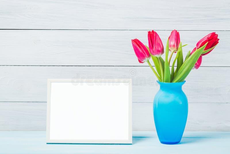 Bunte Tulpe des roten Frühlinges blüht im netten blauen Vase und im leeren Fotorahmen auf hellem hölzernem Hintergrund als Grußka stockbild