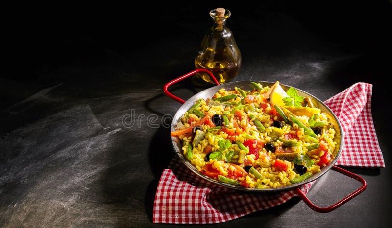 Bunte vegetarische spanische Paella gedient mit Öl lizenzfreie stockfotos