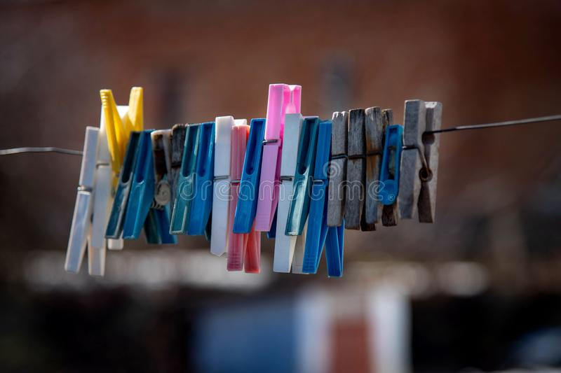 Bunte Wäscheklammer, die an einem Seil hängt Plastik- und hölzerne Wäscheklammern stockfotografie