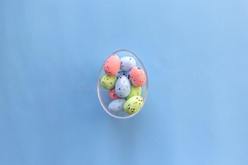 Bunte Wachteleier im großen Glasei auf blauem Hintergrund Gl?ckliches Ostern-Konzept Draufsicht, flache Lage lizenzfreie stockfotos
