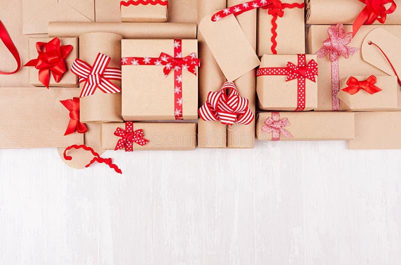 Bunte weiche verschiedene Feiergeschenke mit roten Bögen und Bänder auf weißer hölzerner Tabelle, flache Lage, Grenze lizenzfreies stockbild