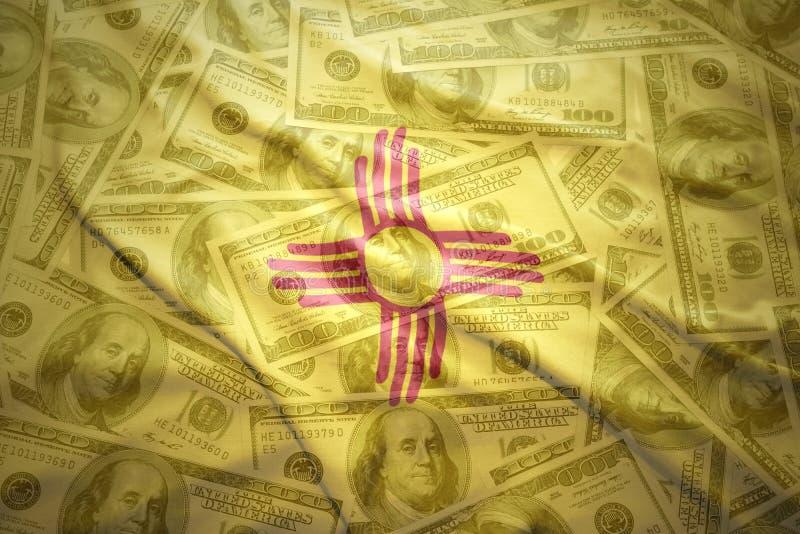 Bunte wellenartig bewegende New-Mexiko Staatsflagge auf einem amerikanischen Dollargeldhintergrund lizenzfreie stockfotografie