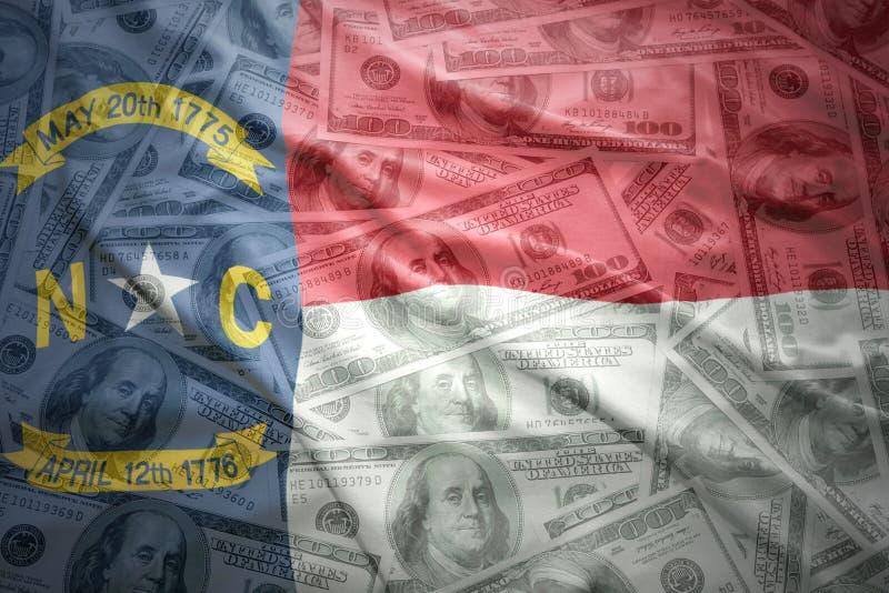 Bunte wellenartig bewegende Nord-Carolinastaatsflagge auf einem amerikanischen Dollargeldhintergrund lizenzfreie stockfotos
