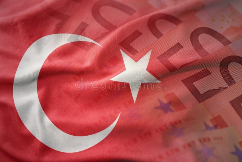 bunte wellenartig bewegende Staatsflagge des Truthahns auf einem Eurogeld-Banknotenhintergrund lizenzfreie stockfotos