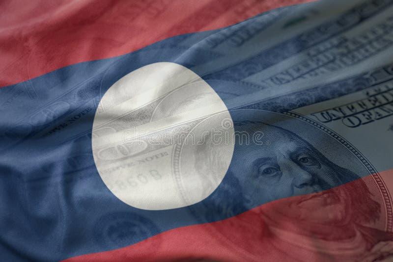 Bunte wellenartig bewegende Staatsflagge von Laos auf einem amerikanischen Dollargeldhintergrund stockbilder