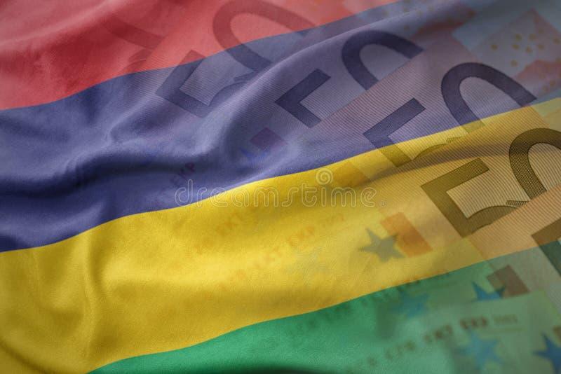 Bunte wellenartig bewegende Staatsflagge von Mauritius auf einem Eurogeld-Banknotenhintergrund lizenzfreie stockfotografie