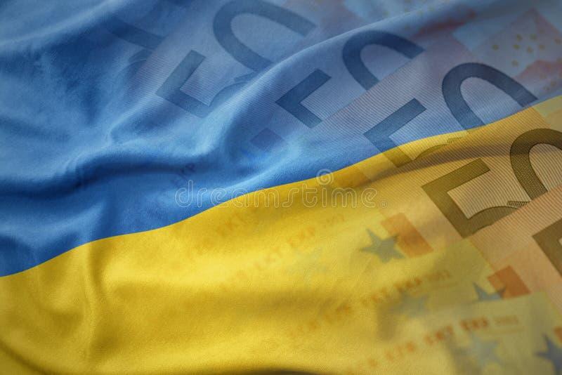 bunte wellenartig bewegende Staatsflagge von Ukraine auf einem Eurogeld-Banknotenhintergrund lizenzfreie stockfotos