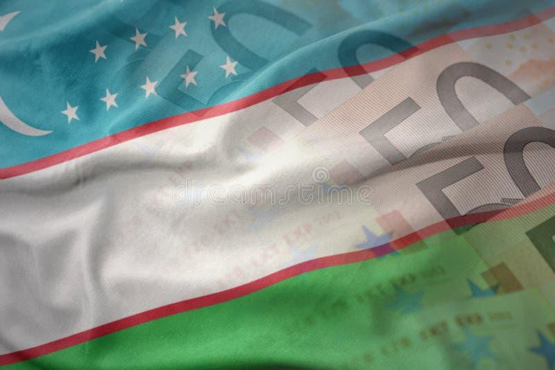 Bunte wellenartig bewegende Staatsflagge von Usbekistan auf einem Eurogeld-Banknotenhintergrund stockfotos