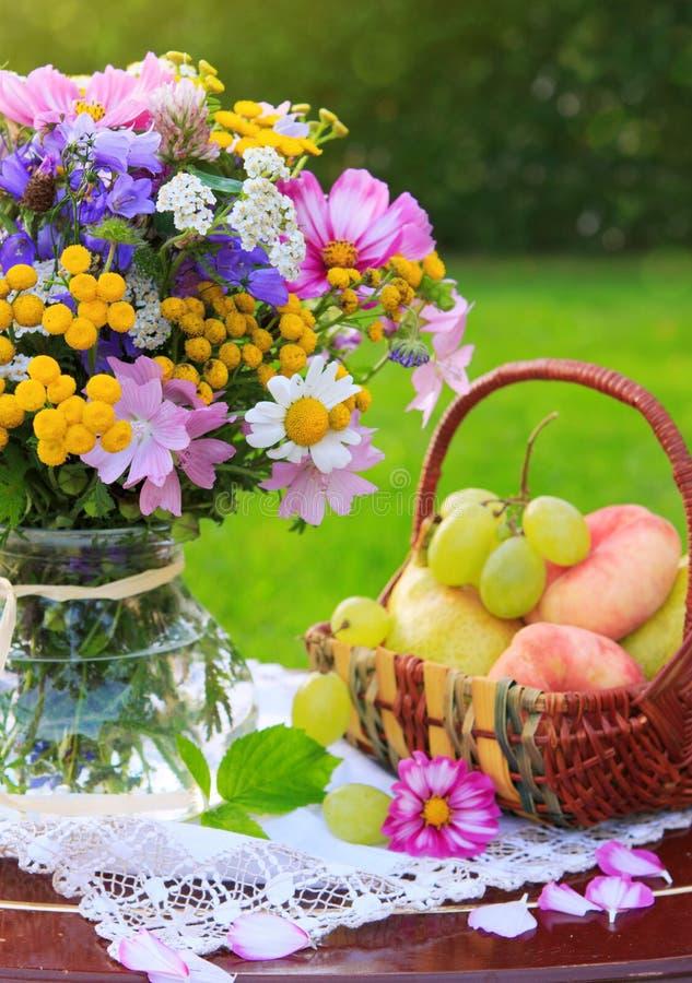 Bunte wilde Blumen und Obstkorb des Blumenstraußes lizenzfreie stockbilder