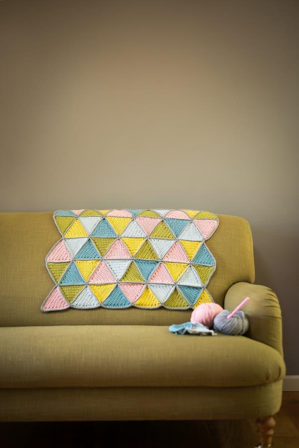 Bunte Woolen Matte, Garn und Häkelnadeln auf Couch lizenzfreies stockbild