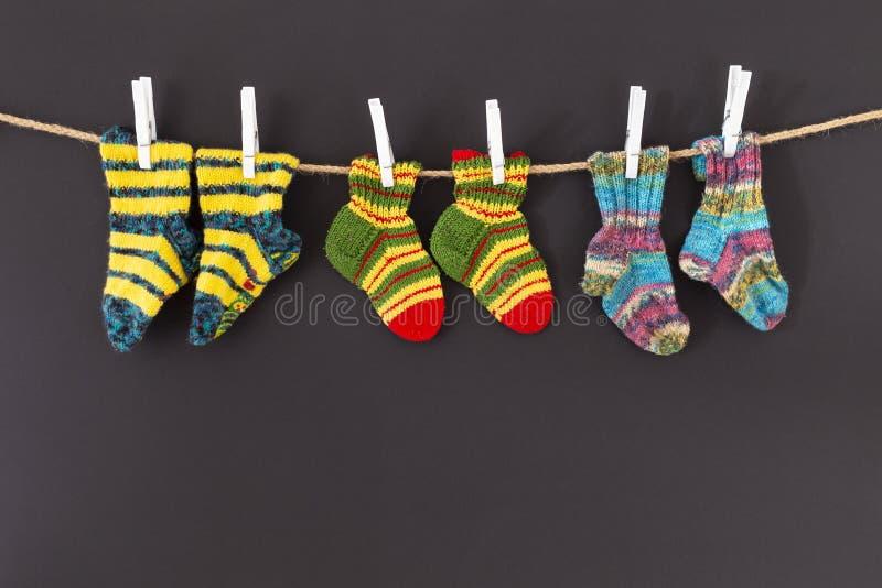 Bunte woolen Socken auf einem Seil auf schwarzem Hintergrund lizenzfreies stockfoto