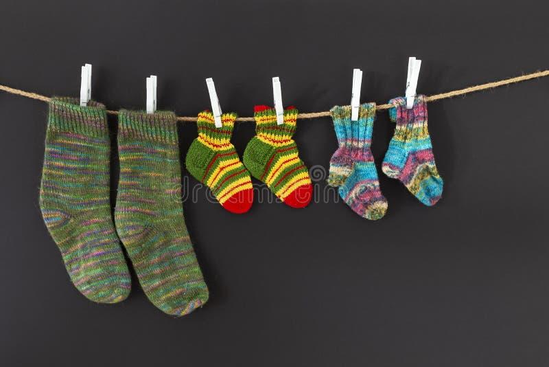 Bunte woolen Socken auf einem Seil auf schwarzem Hintergrund lizenzfreies stockbild