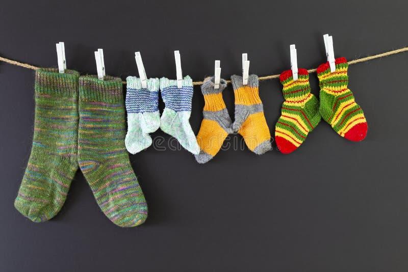 Bunte woolen Socken auf einem Seil auf schwarzem Hintergrund stockfoto