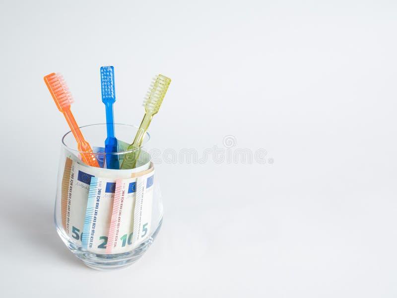 3 bunte Zahnbürsten stehen in einem Glas, in dem Geld im Euro ist stockfotos