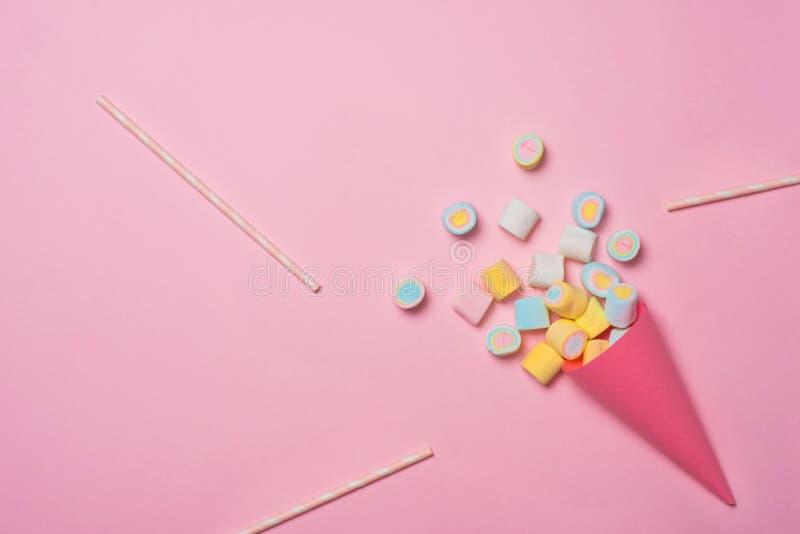Bunte Zusammenstellung der Eibischsüßigkeit in einer Eistüte auf dem rosa Hintergrund angesehen von oben Gummiartige Süßigkeitsve stockbilder