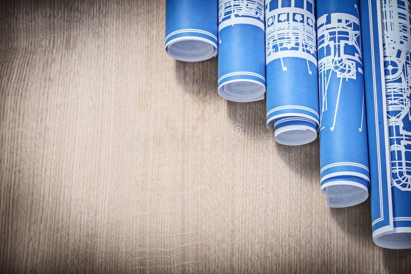 Bunten av blått rullade byggnadsritningar på träbrädehoriz arkivfoton