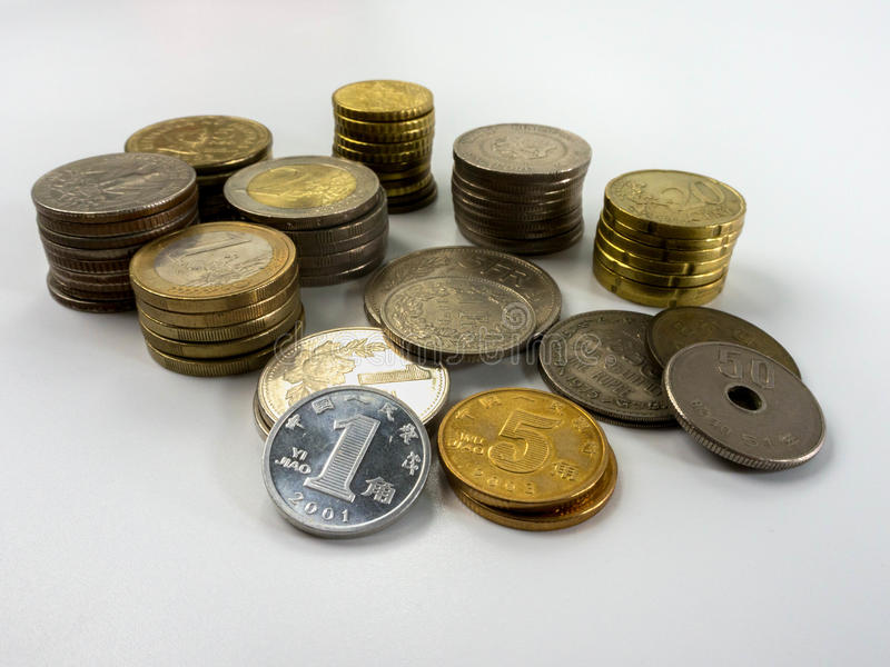 Bunten av det olika myntet skriver på vit bakgrund royaltyfri foto