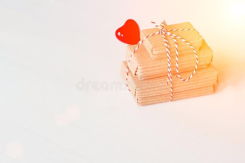 Bunten av handcraft gåvaaskar på vit bakgrund med röd hjärta Kopieringsutrymme, ställe för text Tonat Instagram stil, solljus royaltyfri fotografi