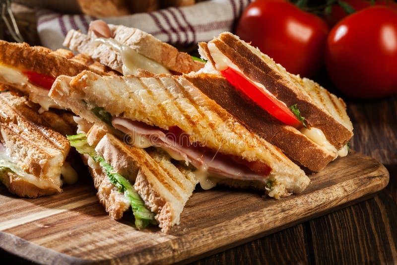 Bunten av panini med skinka, ost och grönsallat skjuter in arkivfoto