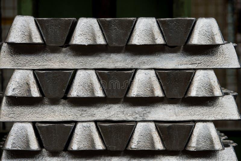 Bunten av rå aluminum tackor i aluminium profilerar fabriken arkivfoton