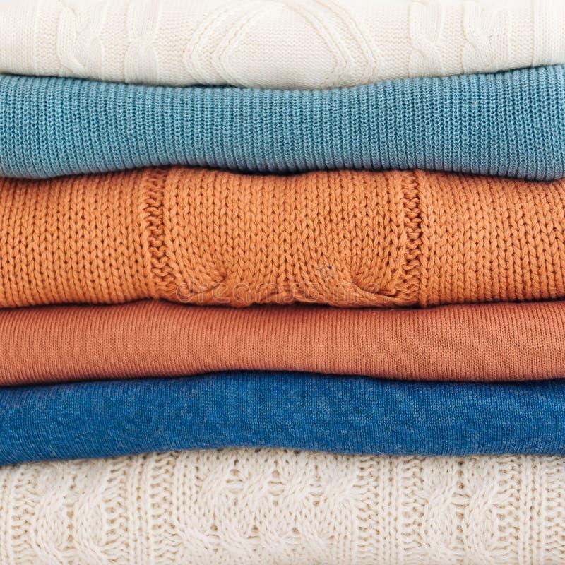 Bunten av varma orange och blåa pastellfärgade tröjor vek royaltyfri fotografi