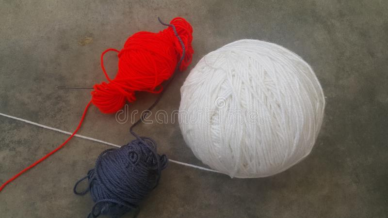 Bunter Ball des Fadenwollgarns für das Stricken auf grauem Bodenhintergrund lizenzfreies stockbild