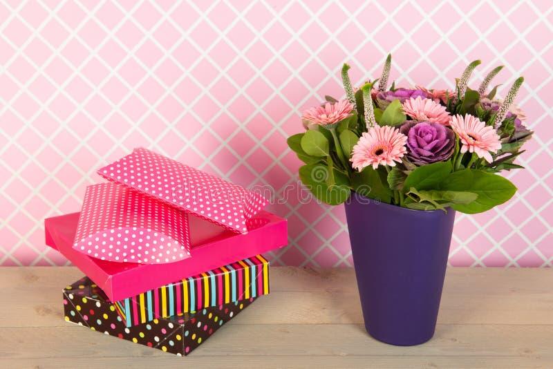 Bunter Blumenstrauß blüht im blauen Vase und in eingewickelten Geschenken lizenzfreie stockfotos
