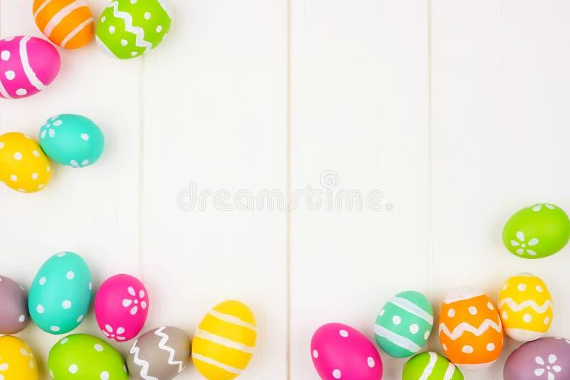 Bunter Easter Egg-Rahmen oder Eckgrenze über einem weißen hölzernen Hintergrund stockbild