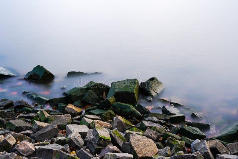 Bunter felsiger Strand nahe nebelhaftem ruhigem Wasser lizenzfreies stockbild