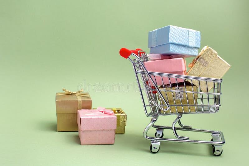 Bunter Geschenkkasten, Supermarktwarenkorb auf grünem Hintergrund stockbilder