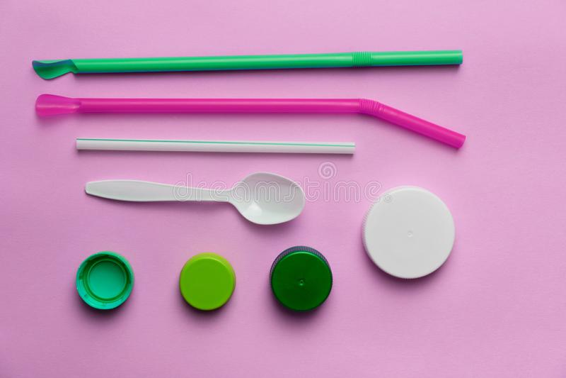 Bunter grün-blauer Deckelkappenstroh-Löffelplastikabfall oder Abfallumweltfragen auf rosa Hintergrund lizenzfreie stockfotos