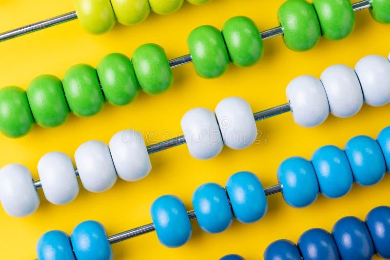 Bunter hölzerner Abakus bördelt auf gelbem Hintergrund, Geschäft fina lizenzfreie stockbilder