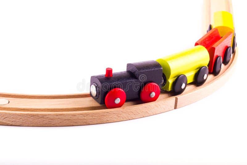 Bunter hölzerner Spielzeugzug auf einer hölzernen Schiene stockfotos