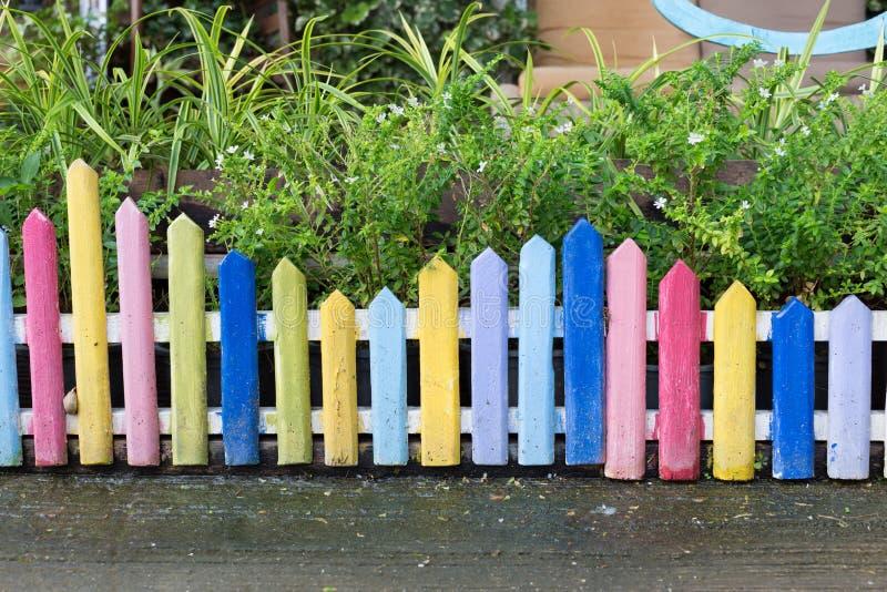 Bunter hölzerner Zaun im kleinen Garten lizenzfreie stockfotos