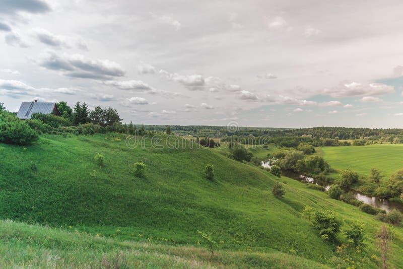 Bunter heller Sunny Landscape mit russischem Landhaus auf H?gel in einer Mitte des Fotos mit einem heller Kontrast-bew?lkten Himm lizenzfreies stockfoto