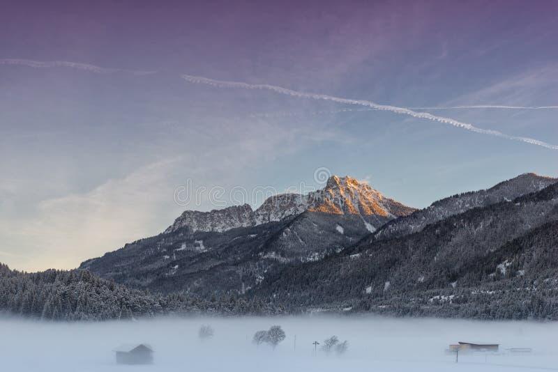 Bunter Himmel bei Sonnenaufgang mit enormem Berg stockbild