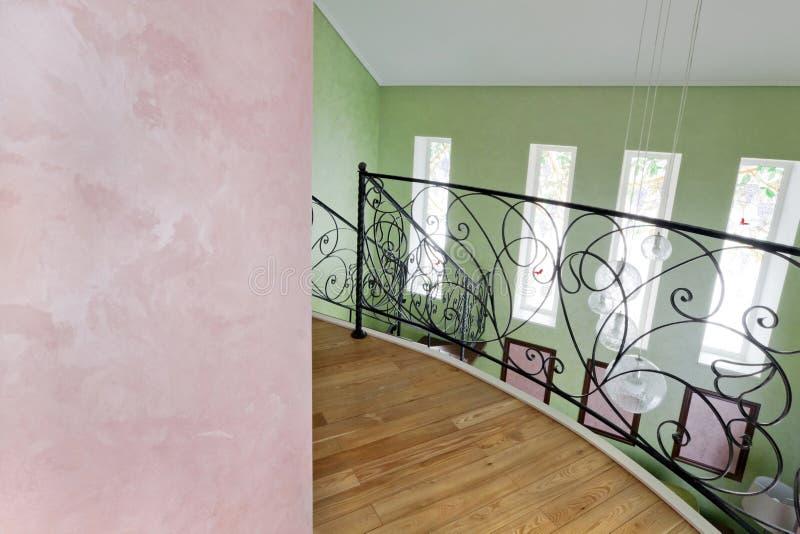 Bunter Innenraum mit dekorativer Beschichtungseide und dem geschmiedeten schwarzen Fechten des zweiten Stocks lizenzfreie stockfotografie