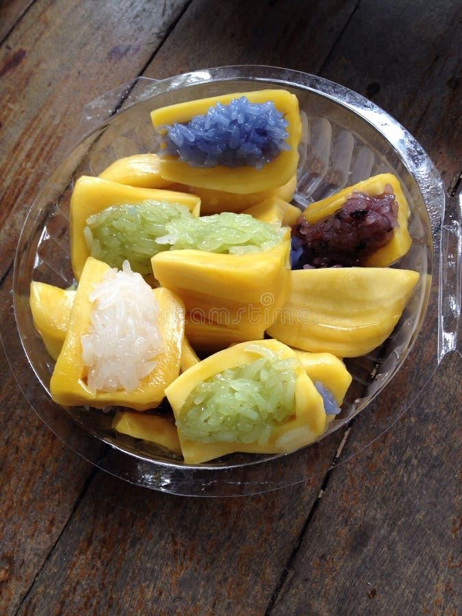 Bunter klebriger Reis des Regenbogens mit Kokosnusscreme innerhalb der Steckfassungsfrucht stockfotos