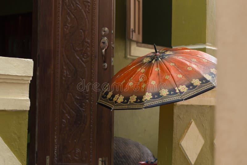 Bunter orange Regenschirm auf dem Portal eines Dorfhauses im nort lizenzfreies stockbild