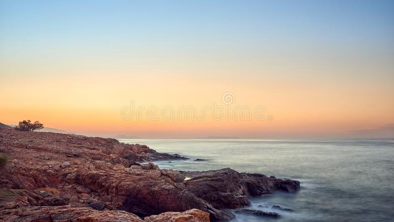 Bunter orange tropischer Sonnenuntergang über einer felsigen Küstenlinie lizenzfreies stockfoto