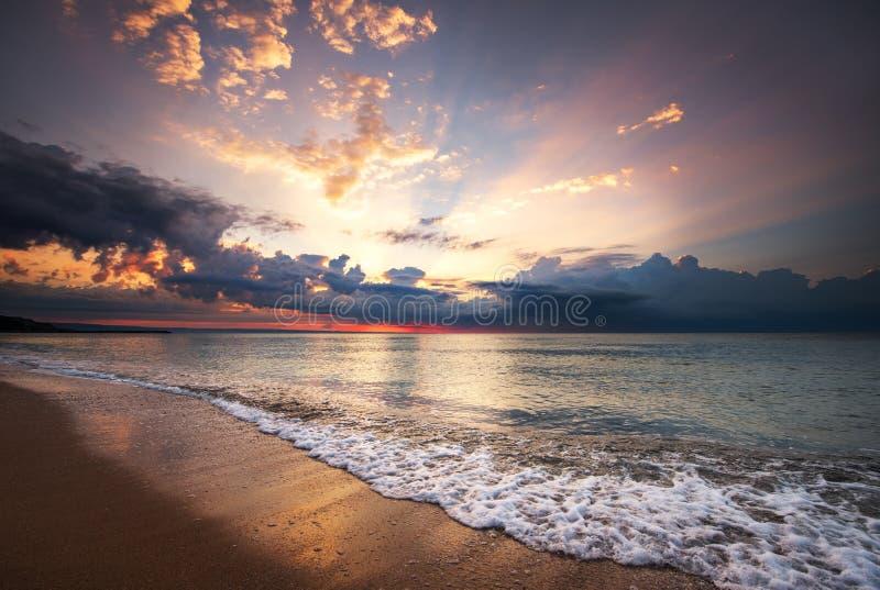 Bunter Ozeanstrandsonnenaufgang mit tiefem blauem Himmel und Sonne strahlt aus stockbild