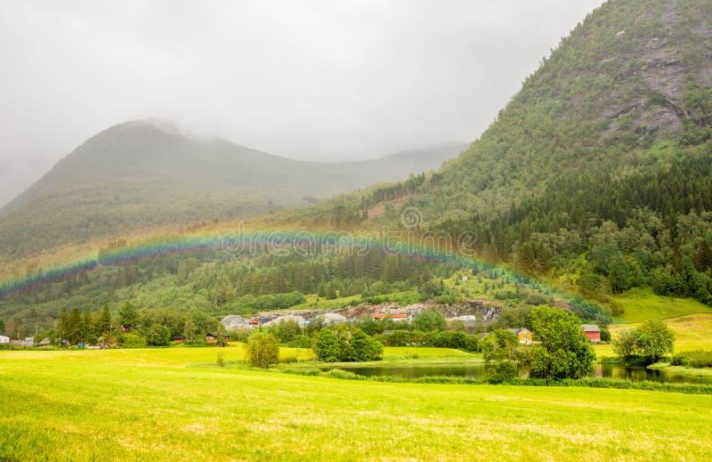 Bunter Regenbogen über den Feldern, dem See und den Häusern von Skei-Dorf, Jølster in Sogn-og Fjordane-Grafschaft, Norwegen stockbilder