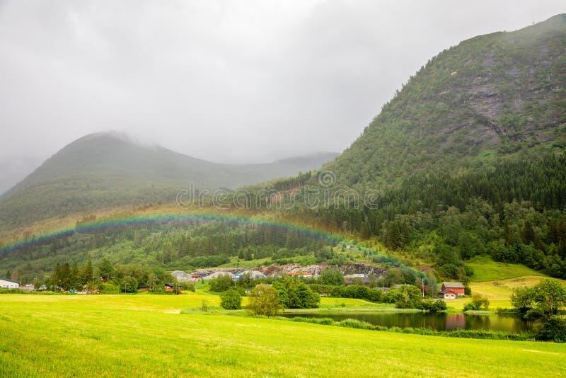 Bunter Regenbogen über den Feldern, dem See und den Häusern von Skei-Dorf, Jølster in Sogn-og Fjordane-Grafschaft, Norwegen stockbild